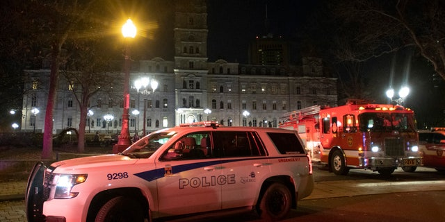 Police cars block the front of the National Assembly early Sunday, Nov. 1, 2020 in Quebec City, Canada.