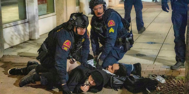 Police arrest a pair of protesters as demonstrators marched around downtown Raleigh after the polls closed Tuesday night. (Travis Long/The News & Observer via AP)