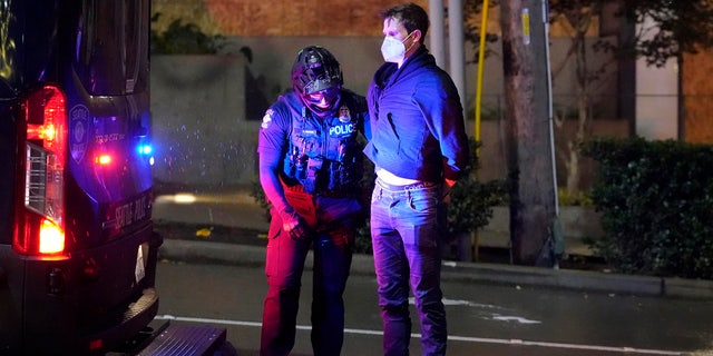 Police officers arrest a person as people march on the night of the election in Seattle, Tuesday, Nov. 3, 2020.