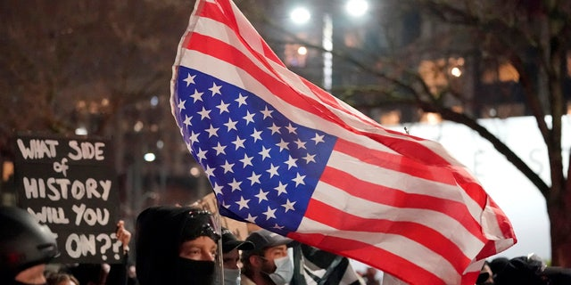A person carries an upside-down flag as people march on the night of the election in Seattle, Tuesday, Nov. 3, 2020.