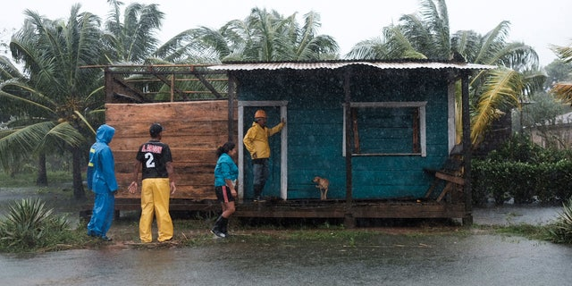 Residents stand outside a home surrounded by floodwaters brought on by Hurricane Eta in Wawa, Nicaragua, Tuesday, Nov. 3, 2020. AP Photo/Carlos Herrera