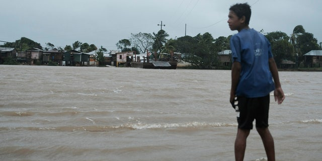 A boy looks over at the river inundated with floodwaters brought on by Hurricane Eta in Wawa, Nicaragua, Tuesday, Nov. 3, 2020.