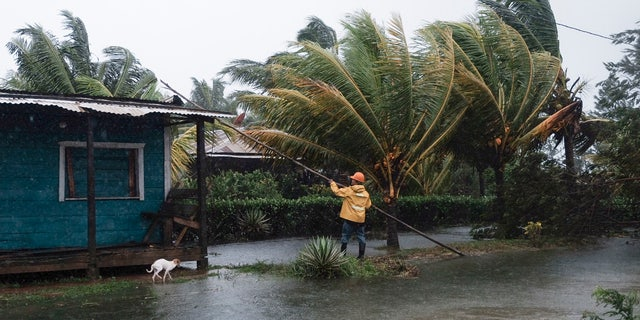 A man fixes the roof of a home surrounded by floodwaters brought on by Hurricane Eta in Wawa, Nicaragua, Tuesday, Nov. 3, 2020.