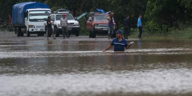 A man walks through a flooded road in Okonwas, Nicaragua, Wednesday, Nov. 4, 2020.