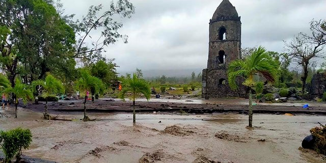 Floodwaters pass by Cagsawa ruins, a famous tourist spot in Daraga, Albay province, central Philippines as Typhoon Goni hit the area Sunday, Nov. 1, 2020.