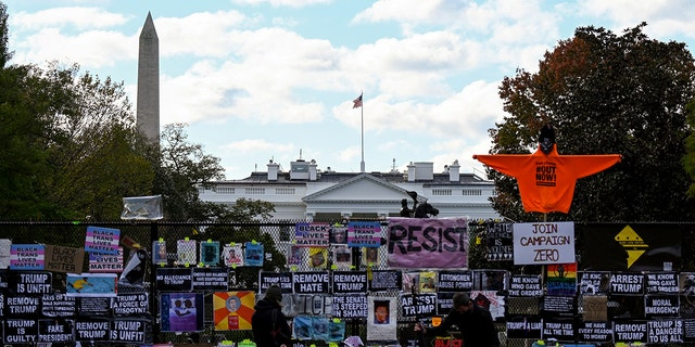 Helicopter passes over the White House, seen behind a fence and protest posters, the day before the U.S. presidential election in Washington, D.C., NOI., novembre 2, 2020. (Reuters/Erin Scott)