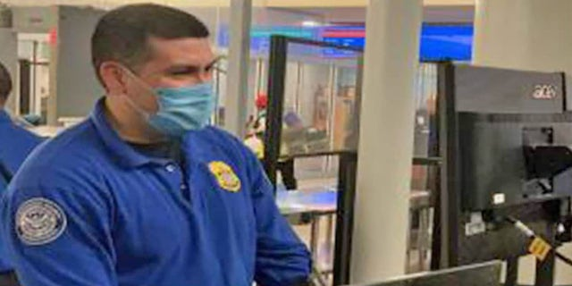 A Transportation Security Administration officer stands at an airport checkpoint.  On Thursday, the TSA urged passengers to behave calmly and respectfully at checkpoints amid a series of incidents involving recalcitrant passengers.