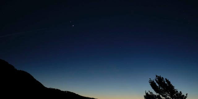 "Saturn, top, and Jupiter, below, are seen after sunset from Shenandoah National Park, Sunday, Dec. 13, 2020, in Luray, Virginia. The two planets are drawing closer to each other in the sky as they head towards a ""great conjunction"" on December 21, where the two giant planets will appear a tenth of a degree apart. Photo Credit: (NASA/Bill Ingalls)"
