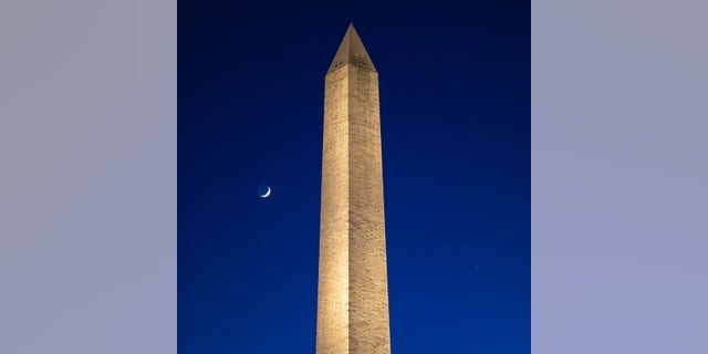 "The Moon, left, Saturn, upper right, and Jupiter, lower right, are seen after sunset with the Washington Monument, Thurs. Dec. 17, 2020, in Washington. The two planets are drawing closer to each other in the sky as they head towards a ""great conjunction"" on December 21, where the two giant planets will appear a tenth of a degree apart. Photo Credit: (NASA/Bill Ingalls)"