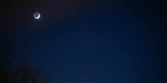 """The Moon, left, Saturn, upper right, and Jupiter, lower right, are seen after sunset from Washington, DC, Thurs. Dec. 17, 2020. The two planets are drawing closer to each other in the sky as they head towards a """"great conjunction"""" on December 21, where the two giant planets will appear a tenth of a degree apart. Photo Credit: (NASA/Aubrey Gemignani)"""