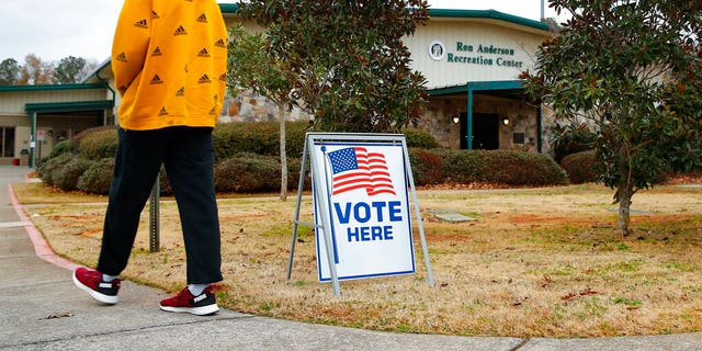 A voter walks to the entrance during early voting for the Senate runoff election, at Ron Anderson Recreation Center, Thursday, Dec. 17, 2020, in Powder Springs, Ga.