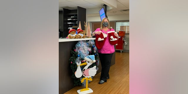 Nurse Lori Shaffer holding up some of the Christmas outfits that she and Pat Vicino made for newborn babies at St. Lucie Medical Center in Port St. Lucie, 佛罗里达.