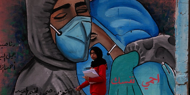 "A student walks past a mural encouraging the wearing of face masks amid the coronavirus pandemic, on the main road of Nusseirat refugee camp, central Gaza Strip, Tuesday, Nov. 24, 2020. Arabic message reads: ""Protect yourself."" (AP Photo/Adel Hana)"