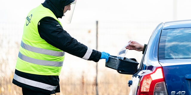 A man wearing a face shield is handed a COVID-19 self-test at a sampling site in a car park at Svågertorp station in Malmö, Sweden, Friday, Nov. 27, 2020. People with symptoms can perform the test on themselves in their vehicle. (Johan Nilsson/TT via AP)