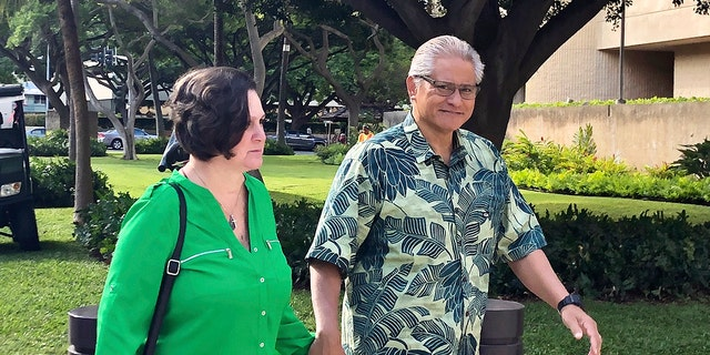 In this March 12, 2019, file photo, retired Honolulu police chief Louis Kealoha and his wife, former deputy city prosecutor Katherine Kealoha, hold hands while walking to U.S. district court in Honolulu. A once-respected, now-estranged power couple are scheduled to be sentenced Monday, Nov. 30, 2020, in Hawaii's biggest corruption case. A jury convicted Katherine and Louis Kealoha of conspiracy in a plot to frame her uncle to keep him from revealing fraud that financed their fancy lives. (AP Photo/Jennifer Sinco Kelleher, File)