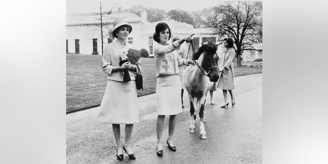 In questo aprile 12, 1962, file photo first lady Jacqueline Kennedy gives a guided tour of the White House grounds to Empress Farah Pahlavi of Iran in Washington. Kennedy leads her daughter Caroline's pony, Macaroni, which had been nuzzling the empress, attracted by the daffodils she was carrying. (AP Photo/Pool)