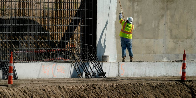 A construction worker paints part of a border wall in Mission, Texas, Monday, Nov. 16, 2020. President-elect Joe Biden will face immediate pressure to fulfill his pledge to stop border wall construction. (AP Photo/Eric Gay)