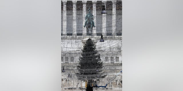 Turned off Christmas lights are backdropped by a 23mt (75 feet) tall fir tree placed in front of Rome's Unknown Soldier monument, Tuesday, Dec. 1, 2020. Still, the large number of daily new COVID-19 cases is worrying, Italian health experts said, especially with the approach of year-end holidays, which could prompt people to ignore social distancing rules and gather in large numbers to celebrate. (AP Photo/Gregorio Borgia)