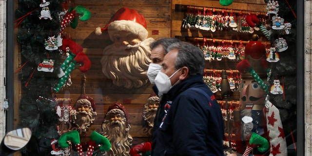 People walk past a shop window adorned with Christmas decorations, in Rome Tuesday, Dec. 1, 2020. Still, the large number of daily new COVID-19 cases is worrying, Italian health experts said, especially with the approach of year-end holidays, which could prompt people to ignore social distancing rules and gather in large numbers to celebrate. (AP Photo/Gregorio Borgia)