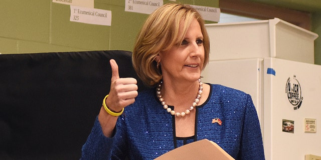 Republican Congresswoman Claudia Tenney signals she successfully cast her ballot after voting at St. George's Church in New Hartford, N.Y. (AP Photo/Heather Ainsworth, File)