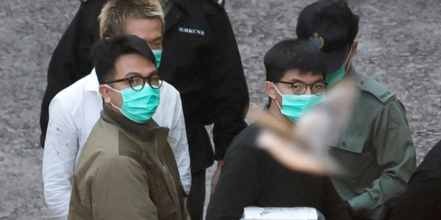 A bird flies as Hong Kong activists Joshua Wong, right, and Ivan Lam, left, are escorted by Correctional Services officers to get on a prison van before appearing in a court, in Hong Kong, Wednesday, Dec. 2, 2020. (AP Photo/Kin Cheung)