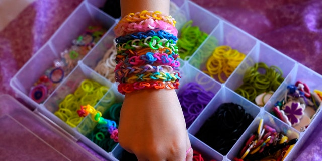 Hayley Orlinsky reaches for a red rubber band Wednesday, Dec. 2, 2020, as she makes a colorful bracelet in the bedroom of her Chicago home. The 7-year-old has spent most of the coronavirus pandemic crafting the bracelets as a fundraiser, earning nearly $20,000, to buy personal protective equipment for the Ann and Robert H. Lurie Children's Hospital. (AP Photo/Charles Rex Arbogast)