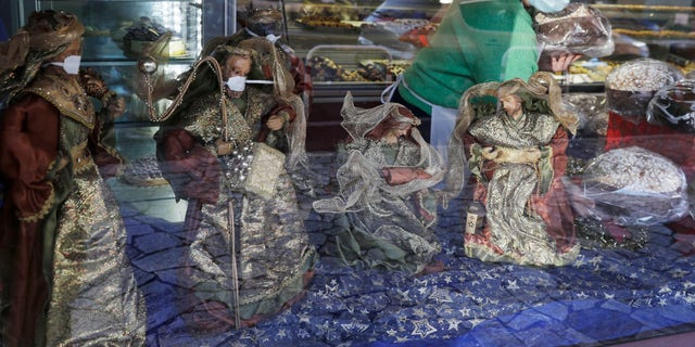 Statuettes of the Wise Kings wearing face masks adorn, along with the Nativity scene, the shop window of a pastry shop selling the traditional Italian Christmas cake, Panettone, in Rome, Wednesday, Dec. 3, 2020. Italy is bracing for new restrictive measures during Christmas and New Year. Prime Minister Giuseppe Conte is expected to sign a new decree on Thursday following a cabinet meeting held on Wednesday night. The rules will likely prevent Italians from traveling across the country during this season holidays in an effort to avoid a new wave of contagion. (AP Photo/Gregorio Borgia