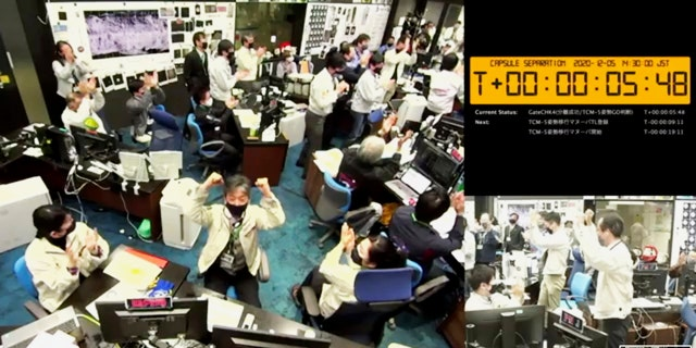 In this image made from video provided by the Japan Aerospace Exploration Agency (JAXA), its members react at the command center in Sagamihara, west of Tokyo, Saturday, Dec. 5, 2020, after JAXA officials confirmed the successful separation of a capsule from the Hayabusa2 spacecraft. (JAXA via AP)