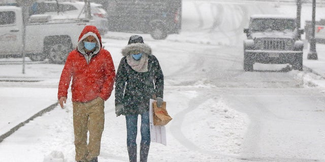 File photo - a couple walks through heavy snow, Saturday, Dec. 5, 2020, in downtown Marlborough, Mass. The northeastern United States is seeing the first big snowstorm of the season.
