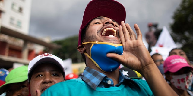 A government supporter shouts in support of parliamentary candidates representing the Great Patriotic Pole party at a closing campaign rally in Caracas, Venezuela, Thursday, Dec. 3, 2020. (AP Photo/Ariana Cubillos)