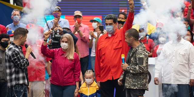 Venezuela's President Nicolas Maduro, right, and first lady Cilia Flores, who is running for a National Assembly seat, wave at supporters during a closing campaign rally for the upcoming parliamentary elections, in Caracas, Venezuela, Thursday, Dec. 3, 2020. Maduro, the hand-picked successor to the late President Hugo Chávez, won a second term in 2018. But his political adversaries and several nations, including the U.S., reject his legitimacy after he banned the most popular challengers. (AP Photo/Ariana Cubillos)