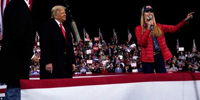 Sen. Kelly Loeffler, R-Ga., speaks as President Trump and Sen. David Perdue, R-Ga., listen at a campaign rally at Valdosta Regional Airport, Saturday, Dec. 5, 2020, in Valdosta, Ga. (AP Photo/Evan Vucci)