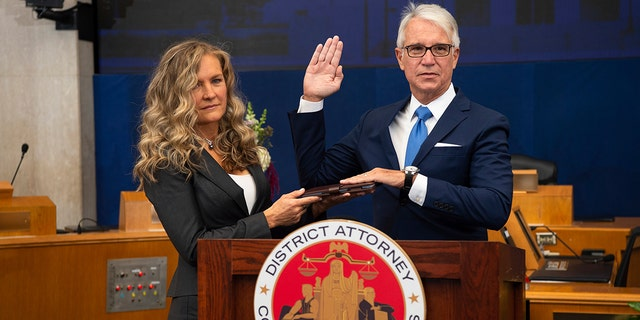 Incoming Los Angeles County District Attorney George Gascon is sworn in as his wife Fabiola Kramsky holds a copy of the Constitution on Dec. 7. (Bryan Chan/County of Los Angeles via AP)