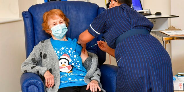 Margaret Keenan, 90, is the first patient in the UK to receive the Pfizer-BioNTech COVID-19 vaccine, administered by nurse May Parsons at University Hospital, Coventry, England, (Jacob King/Pool via AP)