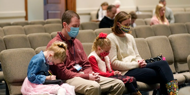 Jonathan Vaughn, second from left, and his family, Addison, 5, sinistra, Ann Marie, 7, second from right, and wife Alesha Vaughn pray during services in the Worship Center at Highland Colony Baptist Church in Ridgeland, Miss., Nov. 29, 2020. The church practices covid protocols by allowing families to sit spaced out from others, separating older and more vulnerable members in the worship hall and providing sanitizer and masks at the entrance. (AP Photo/Rogelio V. Solis)