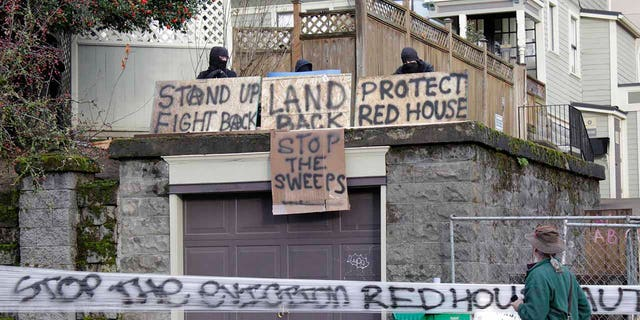 Masked protesters by an occupied home speak with a neighborhood resident opposed to their encampment and demonstration in Portland, Ore., on Wednesday, Dec. 9, 2020. (AP Photo/Gillian Flaccus)