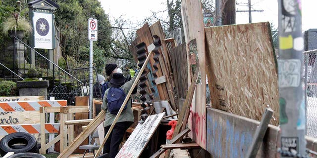 Protesters reinforce their barricades at an encampment outside a home in Portland, Ore., on Wednesday, Dec. 9, 2020. (AP Photo/Gillian Flaccus)