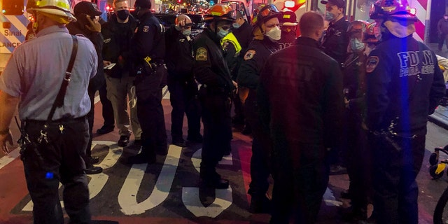 Emergency personnel at an intersection where pedestrians were struck by a car during a protest Friday, Dec. 11, 2020, in New York. The New York Fire Department says six people were hospitalized. (AP Photo/David Martin)