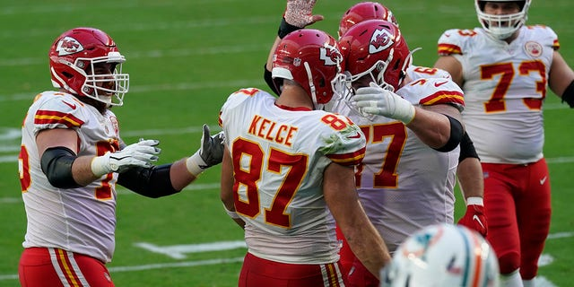 Kansas City Chiefs tight end Travis Kelce (87) is congratulated by his teammates after scoring a touchdown during the first half of an NFL football game against the Miami Dolphins, Sondag, Des. 13, 2020, in Miami Gardens, Fla. (AP Photo / Lynne Sladky)