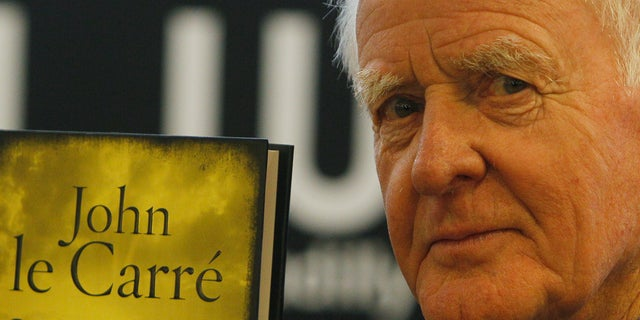 British author John le Carre holds a copy of his new book entitled 'Our Kind of Traitor' at a central London bookstore during a book signing event to mark the launch of the novel in London Thursday, Sept. 16, 2010. (AP Photo/Alastair Grant, file)