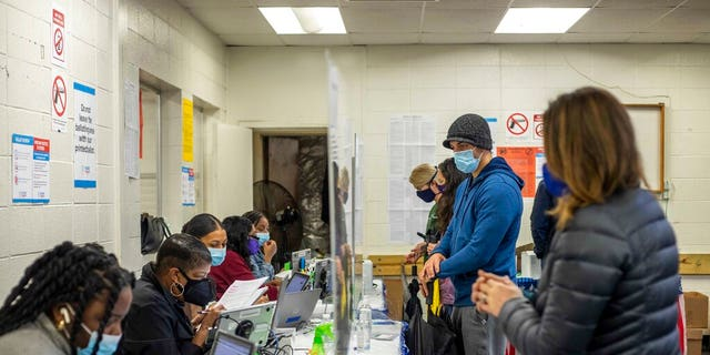 Fulton County elections workers work with voters during early voting in the state's runoff election at Chastain Park Gymnasium in Atlanta's Chastain Park neighborhood, Wednesday, Dec. 16, 2020. (Alyssa Pointer/Atlanta Journal-Constitution via AP)