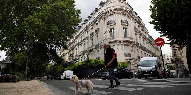 In this Aug.13, 2019 file photo, a man walks his dog next to an apartment building owned by Jeffrey Epstein in Paris. Modeling agent Jean-Luc Brunel who was close to U.S. financier Jeffrey Epstein has been taken into custody in France, suspected of an array of crimes, including the rape of minors and trafficking minors for sexual exploitation, Paris prosecutors said Thursday.(AP Photo/Francois Mori, File)