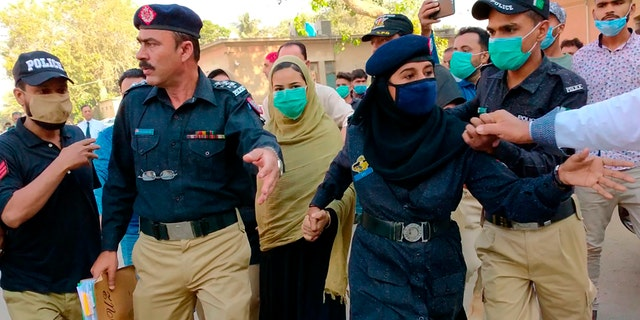 Police officers escort Arzoo Raja, center, a teenage Christian girl, who was allegedly abducted and forced to convert and marry a 44-year old Muslim, while they leave after an appearance before the High Court in Karachi, Pakistan, Nov. 3, 2020.  (AP Photo/Fareed Khan)