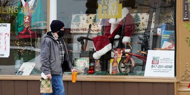 Christmas cards and costumes are displayed in the window at Mid Central Printing &versterker; Mailing store in Wilmette, Siek., Vrydag, Des. 18, 2020. (AP Photo/Nam Y. Huh)