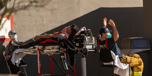 An unidentified patient receives oxygen on a stretcher outside the CHA Hollywood Presbyterian Medical Center in Los Angeles, 12 월. 18, 2020. (AP 통신)