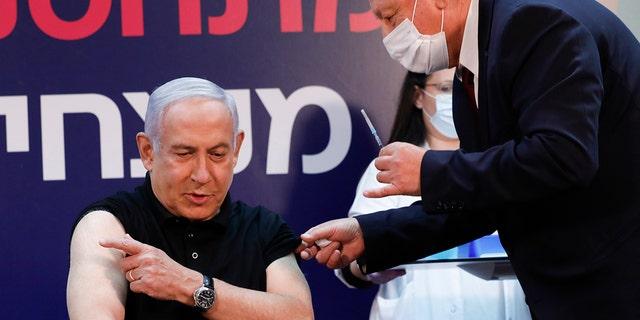 Israeli Prime Minister Benjamin Netanyahu receives a coronavirus vaccine at Sheba Medical Center in Ramat Gan, Israel on Saturday, Dec. 19, 2020. (Amir Cohen/Pool via AP)