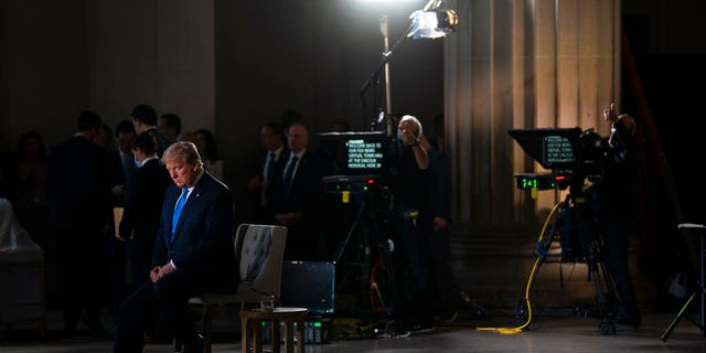 LÊER: President Donald Trump waits for a segment to start during a Fox News virtual town hall from the Lincoln Memorial in Washington.