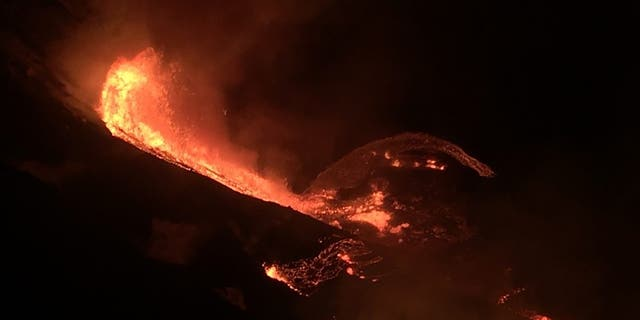 In this photo provided by the U.S. Geological Survey, lava flows within the Halema'uma'u crater of the Kilauea volcano Sunday, Des. 20, 2020. The Kilauea volcano on Hawaii's Big Island has erupted, die VSA. Geological Survey said. (Amerikaanse. Geological Survey via AP)