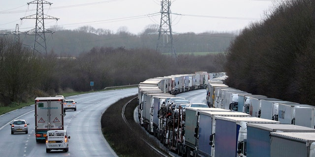 Trucks are parked along the M20 motorway where freight traffic is halted whilst the Port of Dover remains closed, in Ashford, Kent, England, Tuesday, Dec. 22, 2020.  (Andrew Matthews/PA via AP)