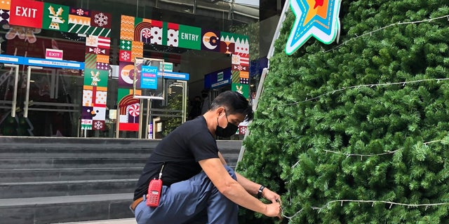 A worker wearing a face mask to help prevent the spread of coronavirus prepares an artificial Christmas tree outside a shopping mall that would normally be busy with foreign tourists in Bangkok on Wednesday, 12 월. 23, 2020. Thailand has kept the coronavirus largely in check for most of the year but is facing a challenge from a large outbreak that threatens to undo months of efforts to contain the virus and hasten recovery of an ailing economy that relies heavily on tourism.(AP Photo/Adam Schreck)